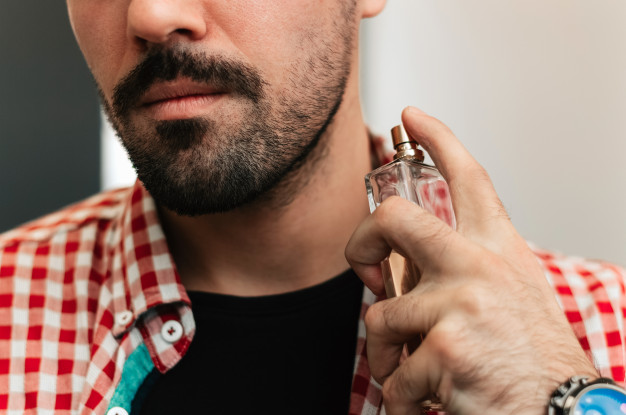handsome-bearded-young-man-spraying-perfume_109710-3527