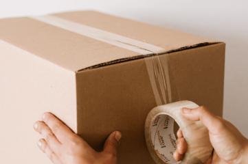 crop-man-sealing-carton-box-with-tape-4498136-min