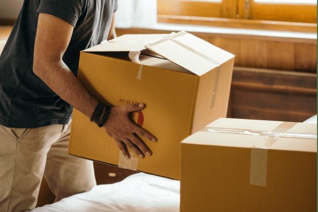 thoughtful-ethnic-man-holding-cardboard-box-preparing-to-4247734-min