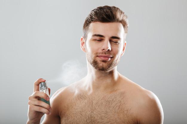 portrait-handsome-half-naked-man-spraying-perfume_171337-2968