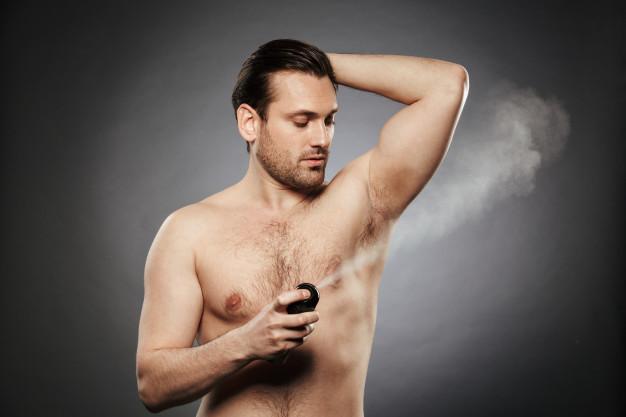 portrait-young-shirtless-man-spraying-deodorant_171337-23922