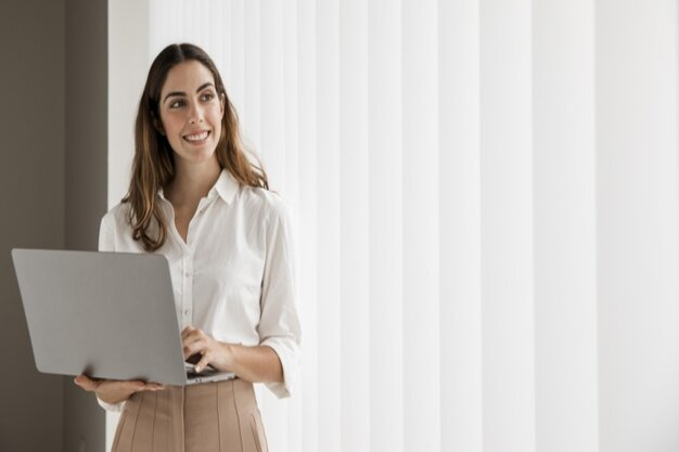 front-view-smiley-elegant-businesswoman-using-laptop-with-copy-space_23-2148788848 (1)