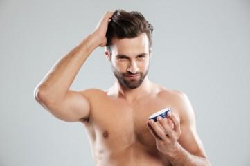 man-straighten-hair-holding-cream-isolated_171337-17353