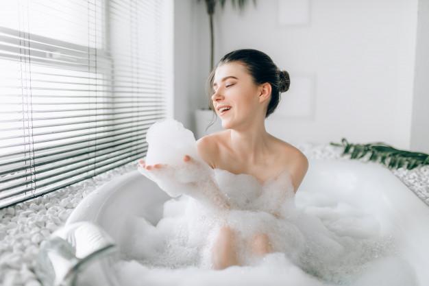 smiling-woman-sitting-bathtube-plays-with-foam-luxury-bathroom-with-window-palm-branch-decor_266732-2977