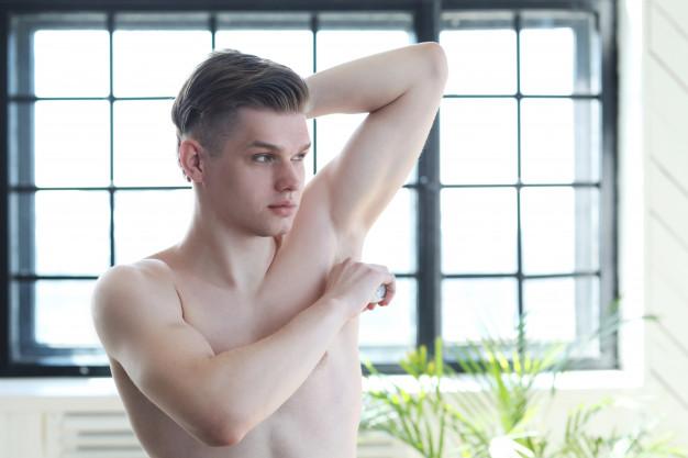 handsome-man-applying-deodorant-armpits_144627-25533