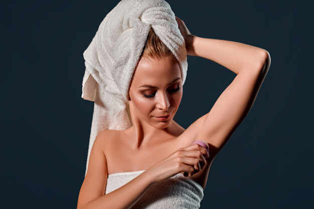 portrait-young-attractive-woman-with-towel-her-head-uses-ball-antiperspirant-black-wall_189498-523